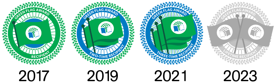 The four badges of the Eco-Schools USA Green Flag Awards. The first is 2017, the second is 2019, and the third is 2021. The final award badge, 2023, is grayed out, signifying it has not yet been conferred.